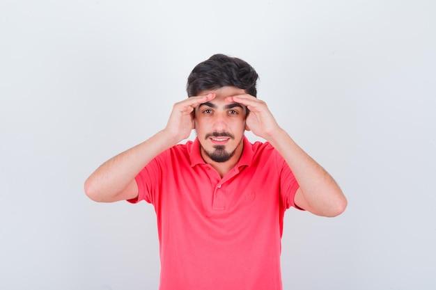 Jeune homme regardant avec les mains au-dessus de la tête en t-shirt rose et à la recherche de joie. vue de face.