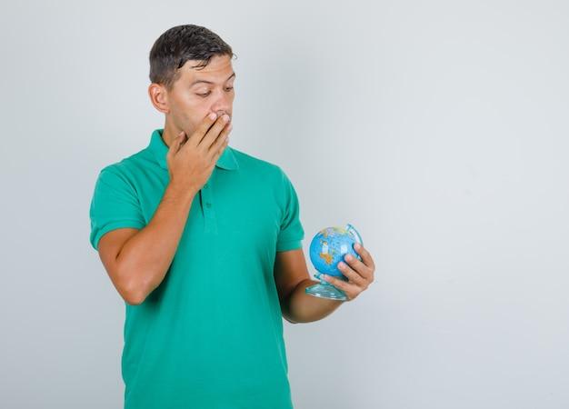 Jeune homme regardant le modèle de globe en t-shirt vert et regardant surpris, vue de face.