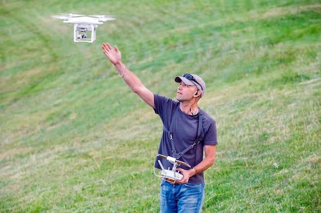 Jeune homme regardant et naviguant dans un drone volant