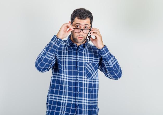 Jeune homme regardant par-dessus des lunettes avec smartphone en chemise à carreaux et à la surprise