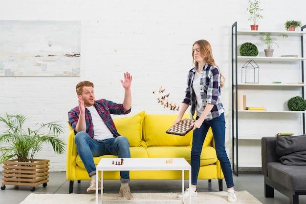 Jeune homme regardant une petite amie en colère jetant les pièces d'échecs dans l'air