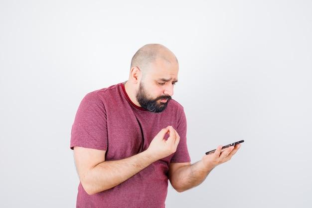 Jeune homme regardant le téléphone et étirant la main pour expliquer quelque chose à quelqu'un en t-shirt rose et l'air lugubre, vue de face.