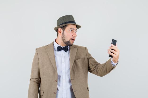 Jeune homme regardant téléphone mobile en costume, chapeau et à la vue choquée, de face.