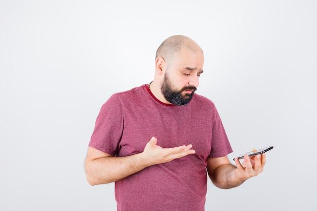 Jeune homme regardant le téléphone et parlant à quelqu'un en t-shirt rose et ayant l'air ennuyé. vue de face.