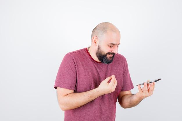 Jeune homme regardant le téléphone et parlant à quelqu'un en t-shirt rose et ayant l'air heureux. vue de face.