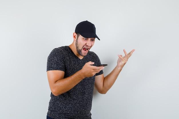 Jeune homme regardant téléphone portable en t-shirt et casquette, jeans et à la colère