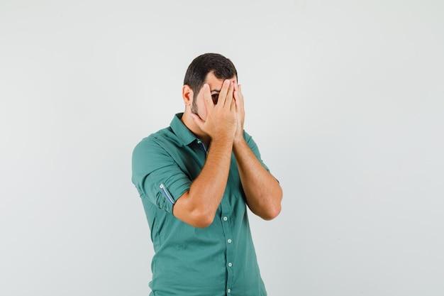 Jeune homme regardant à travers les doigts en chemise verte et l'air inquiet, vue de face.
