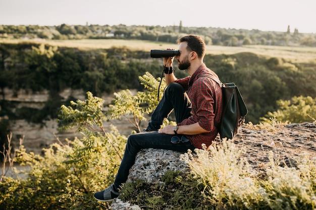 Jeune homme regardant à travers des jumelles, assis sur une falaise dans les montagnes.