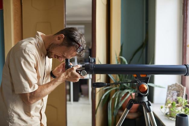 Jeune homme regardant à travers le télescope il regarde les étoiles et les planètes
