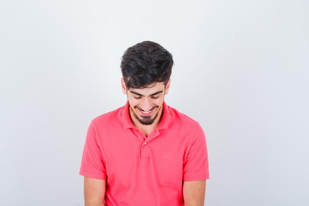Jeune homme regardant vers le bas en t-shirt rose et ayant l'air plein d'espoir, vue de face.