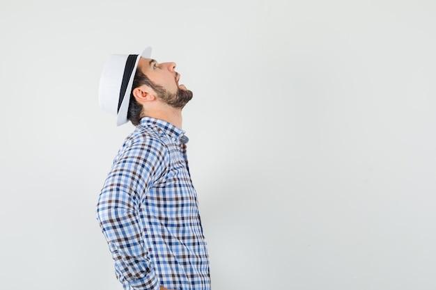 Jeune homme regardant vers le haut en chemise à carreaux, chapeau et à la réflexion. .