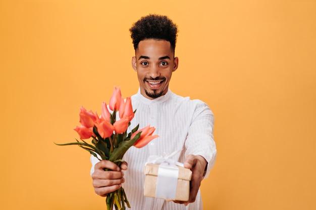 Le jeune homme regarde dans la caméra, tient le bouquet et la boîte avec le cadeau