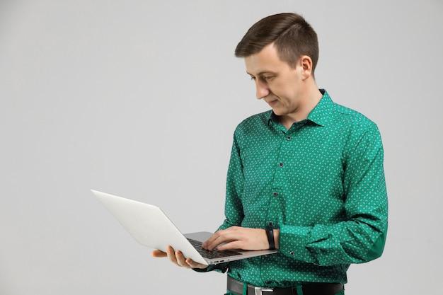 Jeune homme regarde un écran d'ordinateur portable dans ses mains et se tient isolé