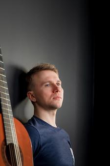 Un jeune homme regarde romantiquement sur le côté à côté d'une guitare contre un mur noir