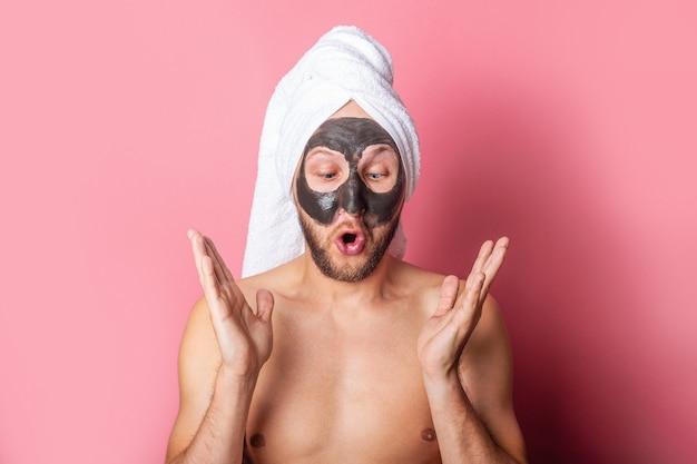 Jeune homme regarde avec surprise un masque cosmétique sur son visage sur fond rose