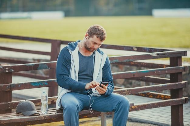 Le jeune homme règle sa musique préférée sur son smartphone avant de s'entraîner
