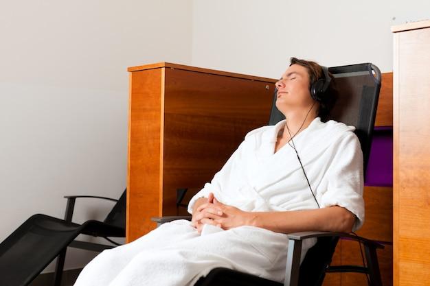 Jeune homme relaxant au spa avec musique