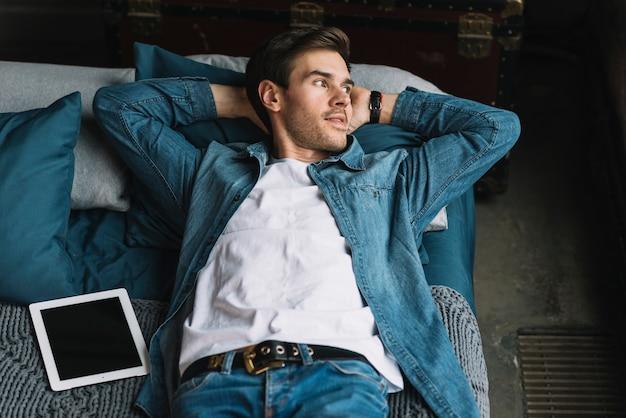 Jeune homme relaxant avec tablette numérique sur le lit