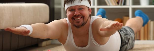 Jeune homme de remise en forme attrayant se trouve sur un tapis gras avec