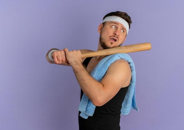 Jeune homme de remise en forme avec bandeau et serviette sur l'épaule tenant une batte de baseball à côté avec une expression confiante debout sur fond violet