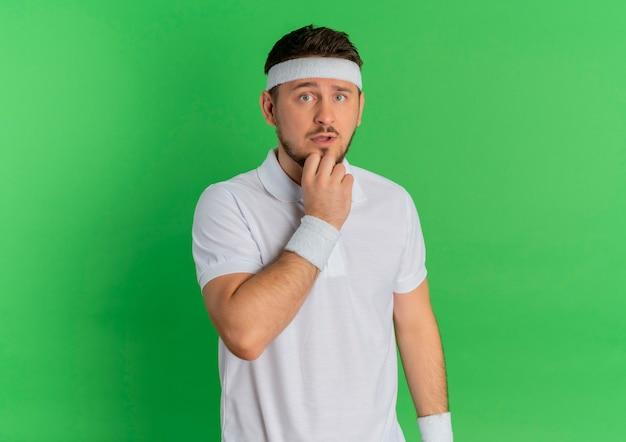 Jeune homme de remise en forme en chemise blanche avec bandeau à l'avant perplexe debout sur le mur vert