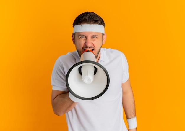 Jeune homme de remise en forme en chemise blanche avec bandeau criant au mégaphone avec une expression agressive debout sur un mur orange