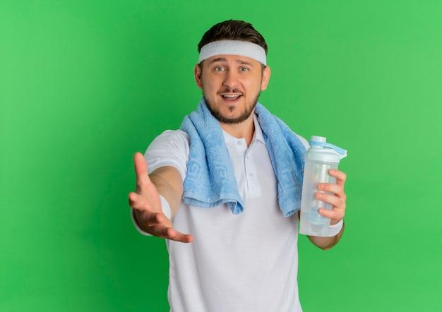 Jeune homme de remise en forme en chemise blanche avec bandeau et serviette autour du cou tenant une bouteille d'eau regardant la caméra en souriant avec le bras debout sur fond vert