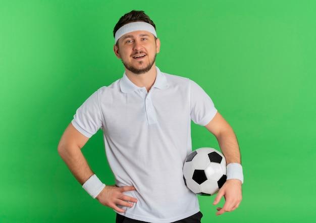 Jeune homme de remise en forme en chemise blanche avec bandeau tenant un ballon de football regardant la caméra en souriant joyeusement debout sur fond vert