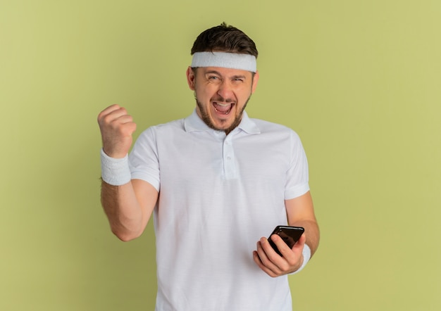 Jeune homme de remise en forme en chemise blanche avec bandeau tenant le smartphone levant le poing heureux et excité debout sur fond d'olive
