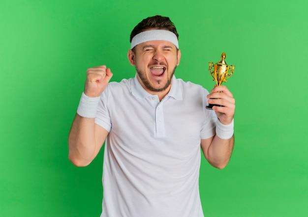 Jeune homme de remise en forme en chemise blanche avec bandeau tenant le trophée heureux et excité debout sur fond vert
