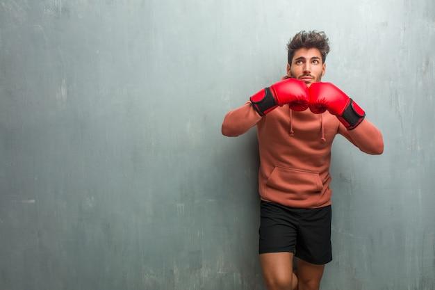 Jeune homme de remise en forme contre un mur de grunge en levant, pensant à quelque chose d'amusant et ayant une idée