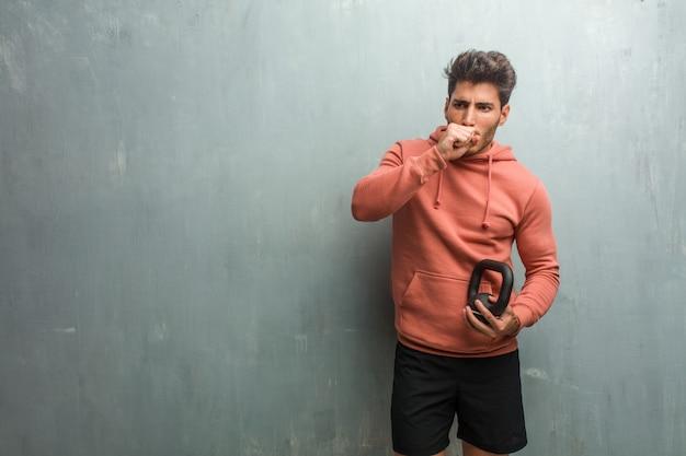 Jeune homme de remise en forme contre un mur de grunge avec un mal de gorge, malade en raison d'un virus