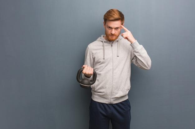 Jeune homme de remise en forme rousse pensant à une idée. tenant un haltère.