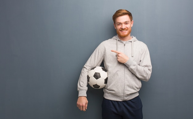 Jeune homme de remise en forme rousse pointant vers le côté avec le doigt. il tient un ballon de football.