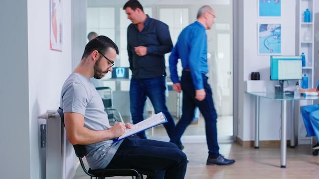 Jeune homme remplissant des documents dans la salle d'attente de l'hôpital. infirmière invitant une femme âgée à l'intérieur de la salle d'examen. patient sortant de l'établissement médical.