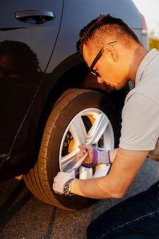 Jeune homme réparant la roue de la voiture