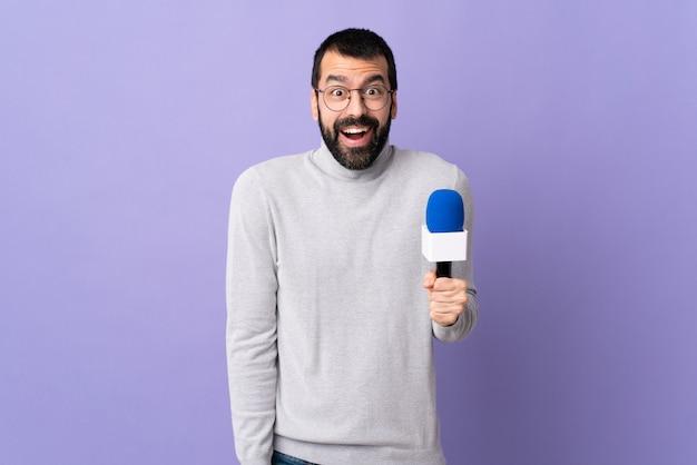 Jeune homme reporter caucasien sur mur violet isolé