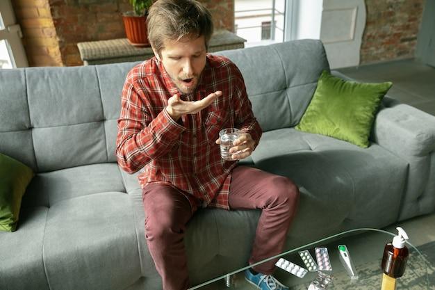 Jeune homme restant à la maison, buvant de l'eau et prenant des pilules