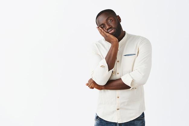 Jeune homme réticent et ennuyé posant contre le mur blanc