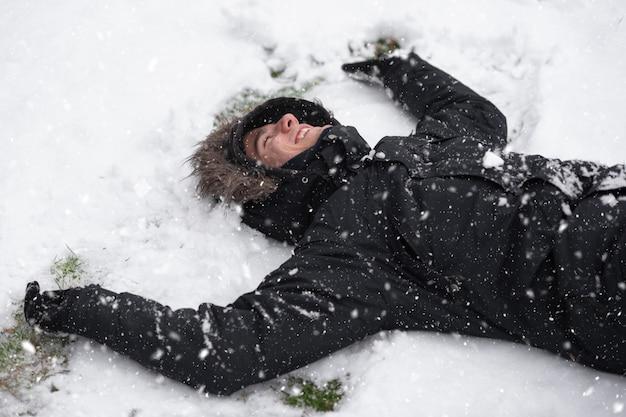 Jeune homme riant, avec une expression heureuse, couvert de neige, gisant sur le sol dans les chutes de neige.
