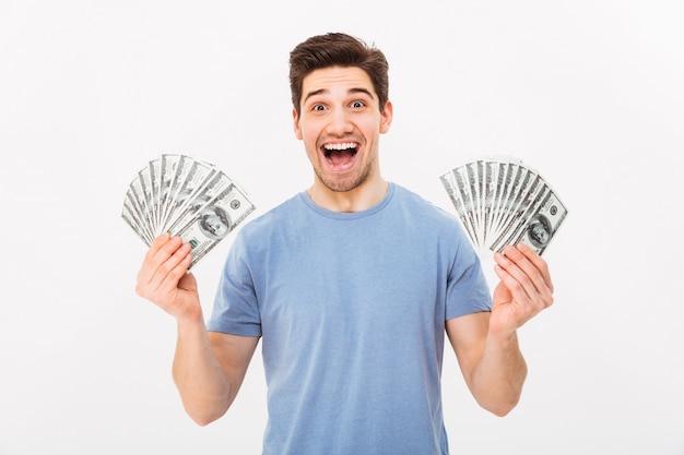 Jeune homme riche en t-shirt décontracté tenant deux fans de billets d'un dollar d'argent avec surprise, isolé sur mur blanc