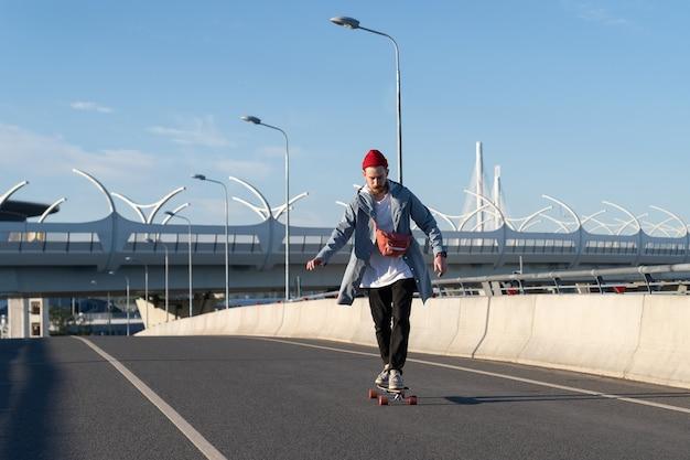 Jeune homme ride longboard sur pont hipster insouciant mâle en tenue de mode à la mode sur skateboard