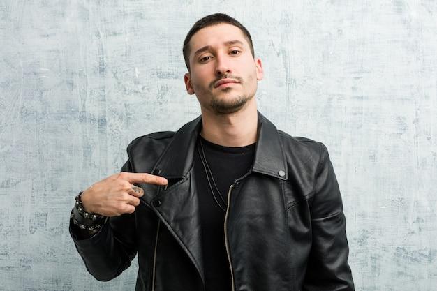 Jeune homme rocker personne pointant à la main vers un espace copie de chemise, fier et confiant