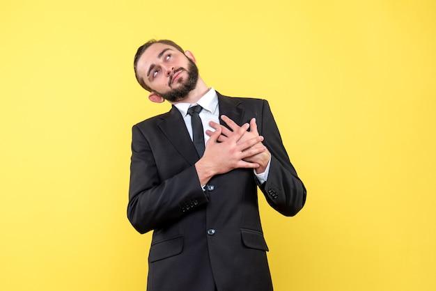 Jeune homme romantique tenant ses mains sur le coeur