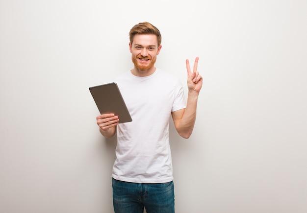 Jeune homme rousse amusant et heureux de faire un geste de victoire. tenant une tablette.