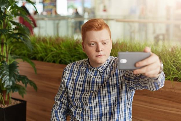 Jeune homme rousse aux taches de rousseur en chemise à carreaux faisant selfie à l'aide de téléphone portable posant contre les plantes vertes ayant une expression sérieuse. homme élégant prenant la photographie avec un téléphone mobile en regardant la caméra.