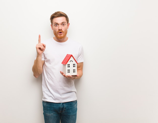 Jeune homme rousse ayant une très bonne idée, concept de créativité. tenir un modèle de maison.