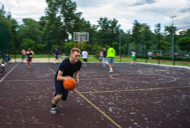 Jeune homme rousse courir et dribbler un ballon de basket à grande vitesse sur un terrain de sport dans la rue pendant la journée flou de mouvement
