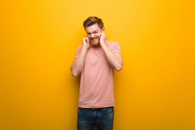 Jeune homme rousse couvrant les oreilles avec les mains