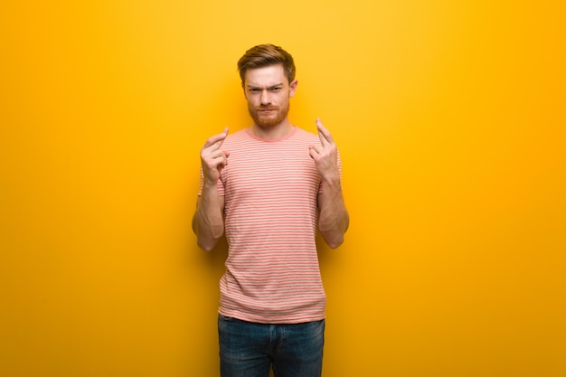 Jeune homme rousse croise les doigts pour avoir de la chance